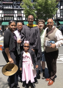 Lance Goodridge standing with his family and Lumbroso in front of Nassau street.  Lance is wearing his black masters graduation gown.
