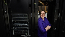 Jennifer Rexford smiling and leaning up against a wall of black computer servers.