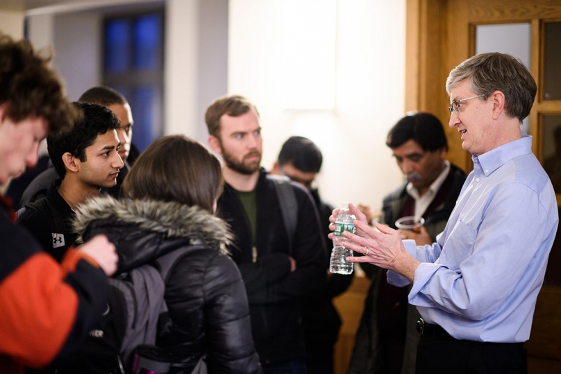 Photo of Professor Ed Felten speaking with students following his presentation.