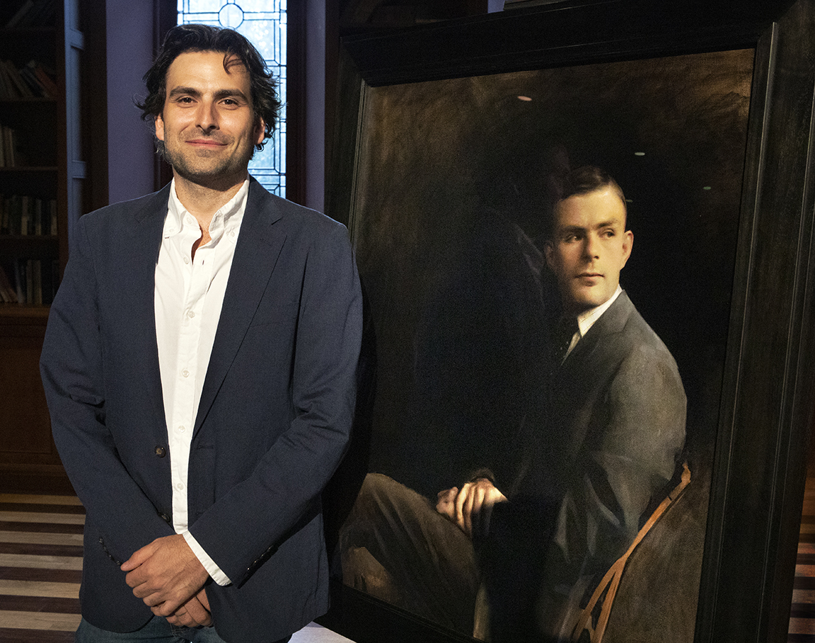 Artist Jordan Sokol standing with the portrait of Alan Turing.