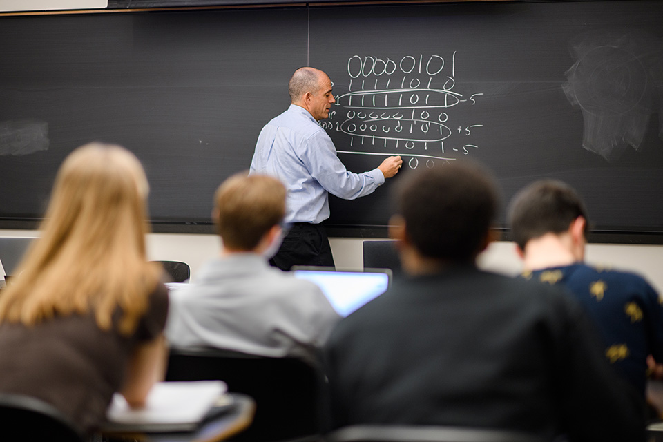 Alan Kaplan standing at the chalkboard in front of the class in COS 126.