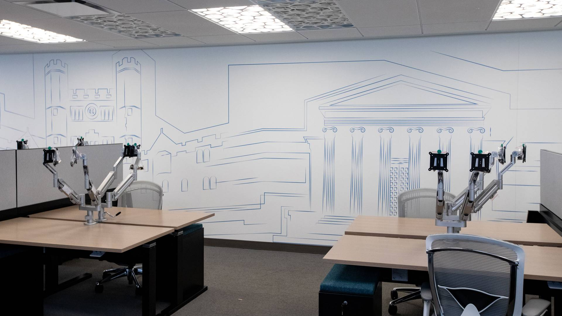 Office interior showing a wall behind desks. The wall has a blue outlined drawing of University buildings.