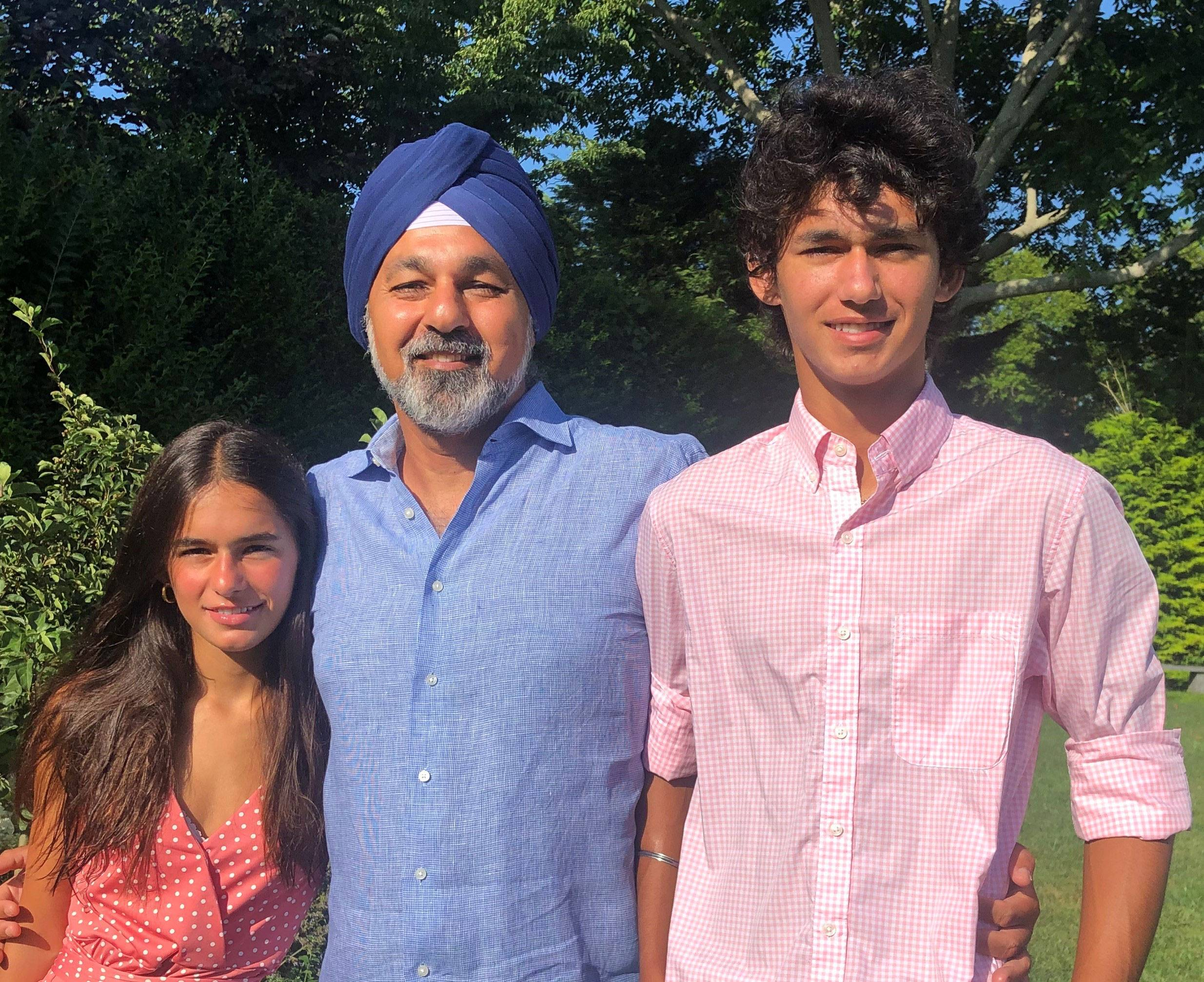 Photo of Jaswinder Pal (JP) Singh with his children, Sophia and Kabir standing outside in front of trees.